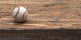 Baseball na starym nieociosanym drewnianym biurku z częściowym plamy tłem Zdjęcia Royalty Free
