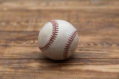 Baseball na starym nieociosanym drewnianym biurku z częściowym plamy tłem Obrazy Stock