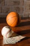 Baseball och basket med dollar Arkivbild