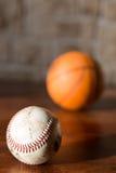 Baseball och basket på en tabell Arkivbild