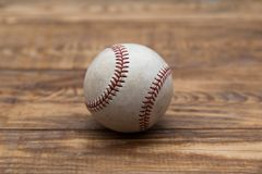 Baseball on a old rustic wooden desk with partial blur background. Old baseball left on a old rustic wooden table. Classic Rawlings ball. Partially blur Stock Images