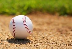 Baseball på fält closeup Arkivbild