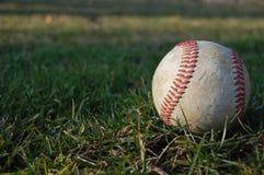 Baseball på gräset Arkivfoto