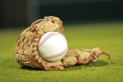 Baseball piłka w rękawiczkowym ob trawy tle Zdjęcia Royalty Free