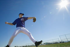 Baseball pitcher, in blue uniform, preparing to throw ball during competitive game, side view (lens flare, surface level, tilt) Royalty Free Stock Photos