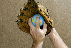 Baseball pitcher holding world globe in glove. Baseball pitcher holding globe in baseball glove royalty free stock photos