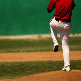 Baseball Pitcher. Baseball player wearing uniform throwing baseball Royalty Free Stock Photos