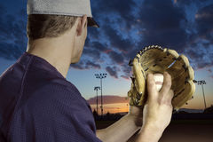 Baseball pitcher ready to pitch in an evening baseball game. A close up view of the baseball pitchers hand just before throwing a fastball in a game. Focus on Royalty Free Stock Photography