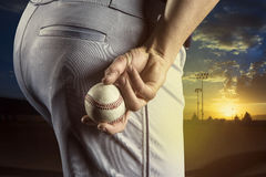 Baseball pitcher ready to pitch in an evening baseball game. A close up view of the baseball pitchers hand just before throwing a fastball in a game. Focus on Royalty Free Stock Photo