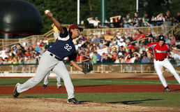 Baseball pitcher throwing ball Stock Images