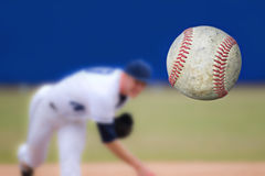 Baseball Pitcher. A baseball pitcher throwing a strike. Selective Focus on the ball coming into close view. Horizontal composition. Copy space