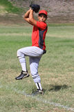 Baseball pitcher winds up to throw the ball Royalty Free Stock Image