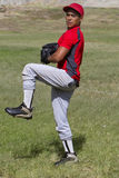 Baseball pitcher winds up to throw the ball Stock Photo