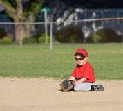 Baseball Player. Tball baseball player sitting on dirt infield Stock Photo