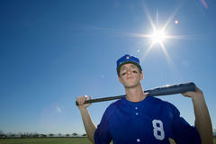 Baseball player, in blue uniform and cap, standing on pitch with bat behind head, front view, portrait (lens flare) Stock Image