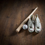 Baseball player equipment. Baseball equipment on hardwood floor including canvas shoes, hardball and bat Royalty Free Stock Image