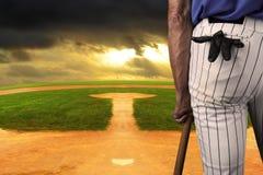 Baseball Player on field leaning on bat stock photo