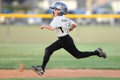 Baseball Player in Gray and Black Uniform Running Stock Photography
