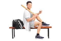 Baseball player holding a bat seated on bench Royalty Free Stock Image
