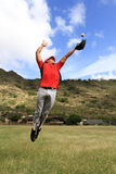 Baseball player jumps high to catch the ball Royalty Free Stock Images