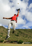 Baseball player jumps to catch a fly ball Stock Photography