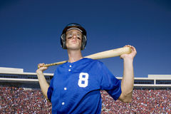 Baseball player, in number �8� blue uniform, helmet and face paint, standing on pitch with bat behind head, low angle view, po Stock Images