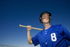 Baseball player, in number �8� blue uniform, helmet and face paint, standing on pitch with bat behind head, low angle view, po Stock Photography
