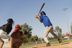 Baseball Player Ready For Strike. Baseball striker ready for a shot with keeper and umpire in position stock image