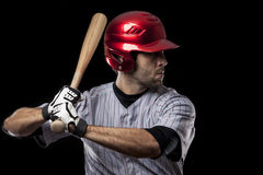 Baseball Player on a red uniform. Baseball Player on a red uniform ready to swing, on a black background. Studio Shot Stock Images