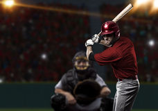 Baseball Player. With a red uniform on baseball Stadium Stock Photo