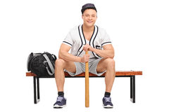 Baseball player sitting on bench and holding a bat Stock Photos