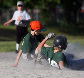 Baseball player sliding into b. Ase during game Stock Image
