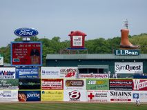 Free Baseball Player Stands In The Outfield With Ads On Wall Including LL Bean, Ford, Subway, Dunkin Donuts Royalty Free Stock Image - 149123806