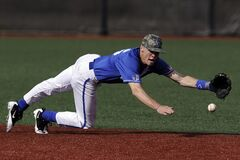 Baseball Player Wearing Blue and White Jersey Catching Baseball Royalty Free Stock Photos
