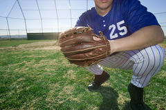 Baseball player, wearing number �25� blue uniform and glove, crouching on pitch, close-up, low section Stock Images