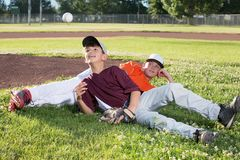 Baseball Players Relaxing. Boys on grass baseball field relaxing in their jerseys and tossing a baseball stock photos