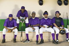 Baseball Players Sitting In Dugout. Tired baseball players sitting side by side in dugout stock photography