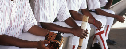 Baseball Players Sitting Together In Dugout. Midsection of baseball players sitting together in dugout stock images
