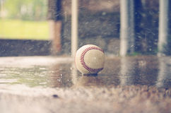 Baseball in the Rain. Old leather baseball laying on the ground wet from rain. Shows weather in sports Stock Photography