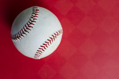Baseball on red background. Old white baseball showing seams on red background, showing sports equipment from above. Ball is round and shows worn spots on Stock Images