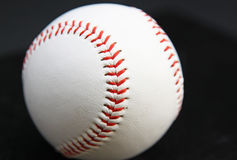 Baseball Seam. Clean, new baseball close up on the seam and  in dark background Royalty Free Stock Photos