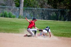 Teenage baseball shortstop tagging player out at second base. Baseball shortstop tagging out a player sliding at second base Stock Photos