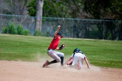 Teenage baseball shortstop tagging player out at second base. Baseball shortstop tagging a player out at second base that was sliding Royalty Free Stock Photo