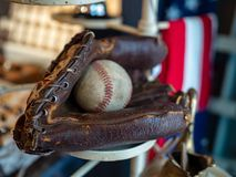 Baseball sitting in old fashioned glove with American flag in background stock photography