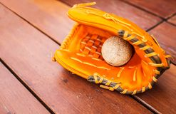 Baseball, Softball with leather mitt glove on wood table floor background with copy space. Sport Recreation Theme royalty free stock photography