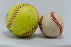 Baseball and softball on a white background. Used baseball and softball side-by-side on a white background and shadowed stock images