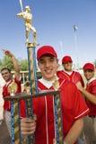 Baseball-Spieler, der Trophäe hält Stockbild
