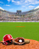 Baseball Stadium With Equipment and Copy Space. Baseball stadium full of fans in the stands with baseball helmet, bat, glove and ball on infield dirt clay Royalty Free Stock Photography