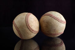 Baseball Still Life. Two worn baseballs sit side by side on a black background.  The reflection of the balls are seen in the photo Stock Photos