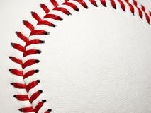 Baseball Stitching Curve. The curved red stitches of a baseball framing area for copy on white leather baseball surface Royalty Free Stock Photos